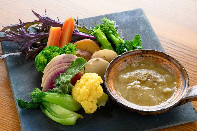旬菜たっぷりのカニ味噌入りバーニャカウダは、ミニ880円、2~3人前1,400円(写真はミニ)。アンチョビや生クリームをカニ味噌ベースで仕上げたソースに野菜をつけて。常時10種類以上が盛られる野菜は、店主の実家で栽培されたもの三次、倉橋が中心で認証が取れていないものでも農薬は不使用だという